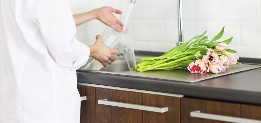 Young woman rinsing and cutting flowers and pouring water into the vase in kitchen sink. Close up